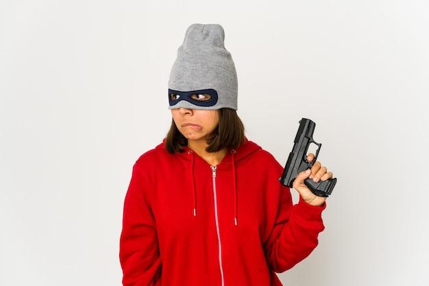 Mulher hispânica jovem ladrão usando uma máscara confusa, sente-se duvidosa e insegura.