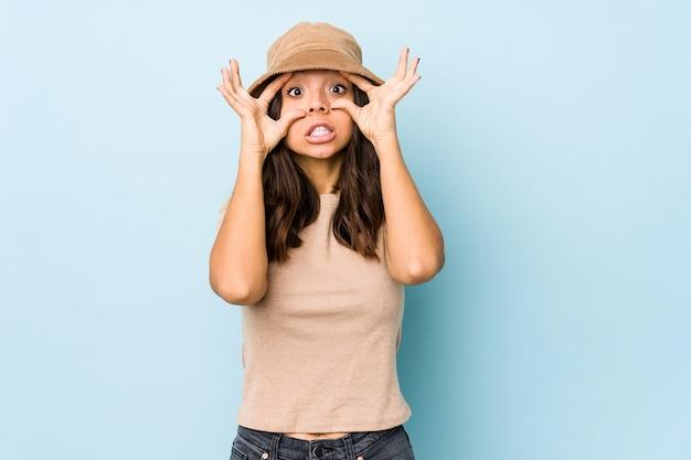 Mulher hispânica jovem mestiça isolada mantendo os olhos abertos para encontrar uma oportunidade de sucesso.