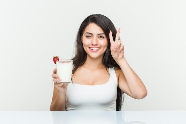 Mulher hispânica jovem segurando um smoothie mulher hispânica jovem segurando um abacate mostrando sinal de vitória e sorrindo amplamente. <mixto>
