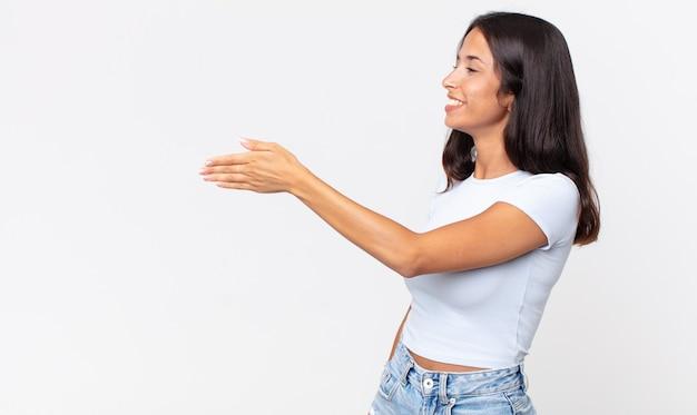 Mulher hispânica muito magra sorrindo, cumprimentando você e oferecendo um aperto de mão para fechar um negócio