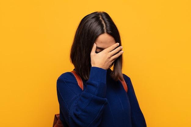 Mulher hispânica parecendo estressada, envergonhada ou chateada, com dor de cabeça, cobrindo o rosto com a mão