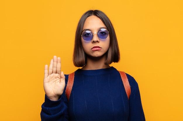 Mulher hispânica parecendo séria, severa, descontente e irritada mostrando a palma da mão aberta fazendo gesto de parada