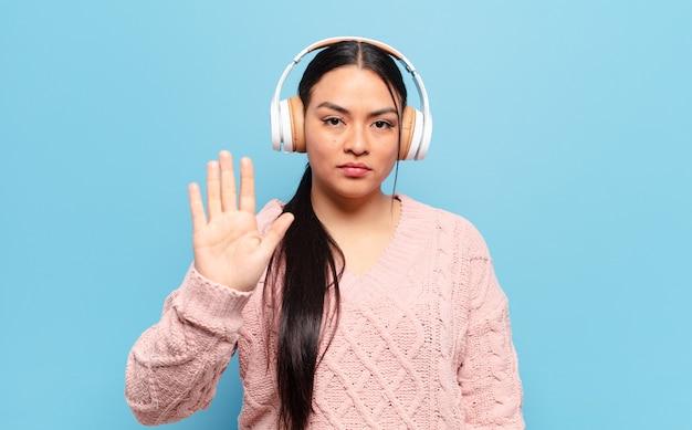 Mulher hispânica parecendo séria, severa, descontente e irritada mostrando a palma da mão aberta fazendo gesto de pare