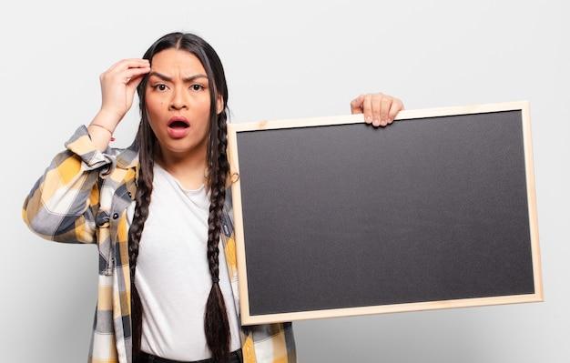 Mulher hispânica parecendo surpresa, boquiaberta, chocada, percebendo um novo pensamento, ideia ou conceito