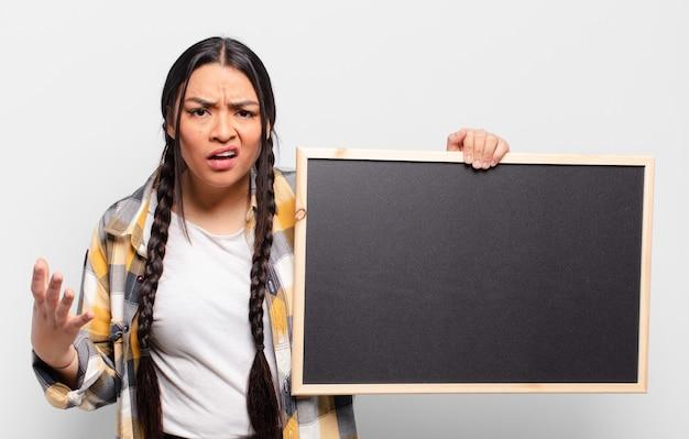 Mulher hispânica parecendo zangada, irritada e frustrada gritando wtf ou o que há de errado com você