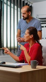 Mulher hispânica pedindo ajuda a collague sentado em frente ao pc em um escritório moderno. equipe trabalhando em um local de trabalho profissional em uma empresa corporativa pessoal, digitando no teclado do computador, olhando para a área de trabalho