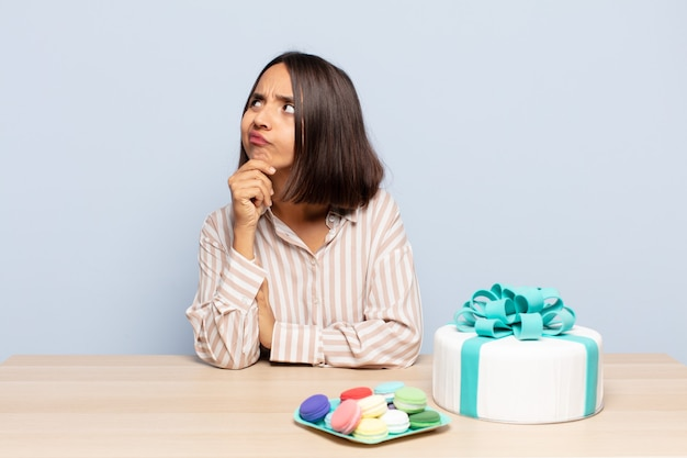 Mulher hispânica pensando, sentindo-se duvidosa e confusa, com diferentes opções, imaginando qual decisão tomar