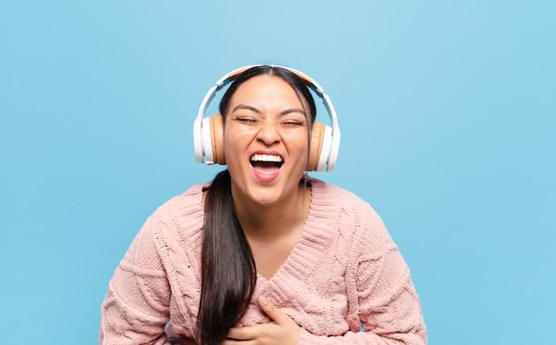 Mulher hispânica rindo alto de alguma piada hilária, sentindo-se feliz e alegre