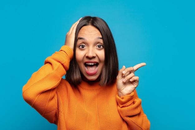 Mulher hispânica rindo, parecendo feliz, positiva e surpresa, percebendo uma ótima ideia apontando para o espaço lateral da cópia