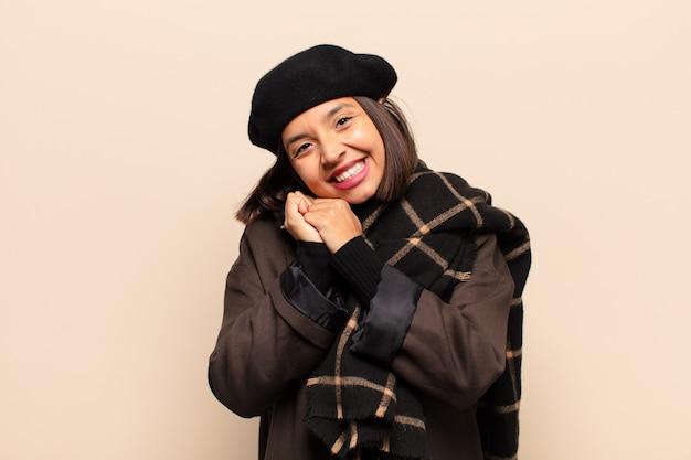 Mulher hispânica se apaixonando e parecendo fofa, adorável e feliz, sorrindo romanticamente com as mãos ao lado do rosto