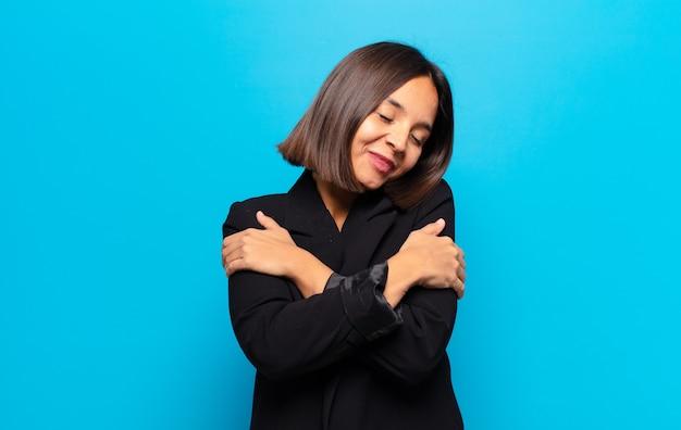 Mulher hispânica se sentindo apaixonada, sorrindo, se abraçando e se abraçando, permanecendo solteira, sendo egoísta e egocêntrica