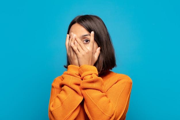 Mulher hispânica se sentindo assustada ou envergonhada, espiando ou espionando com os olhos semicobertos pelas mãos
