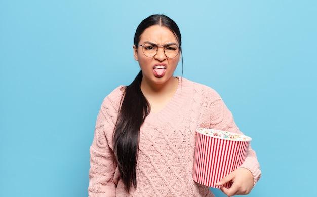 Mulher hispânica se sentindo enojada e irritada, mostrando a língua, não gostando de algo nojento e nojento