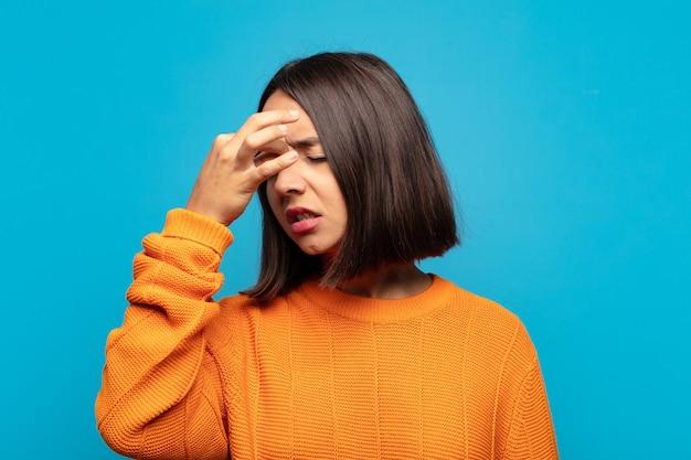 Mulher hispânica se sentindo estressada, infeliz e frustrada, tocando a testa e sofrendo de enxaqueca ou forte dor de cabeça