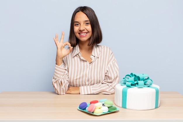 Mulher hispânica se sentindo feliz, relaxada e satisfeita, mostrando aprovação com gesto de ok, sorrindo