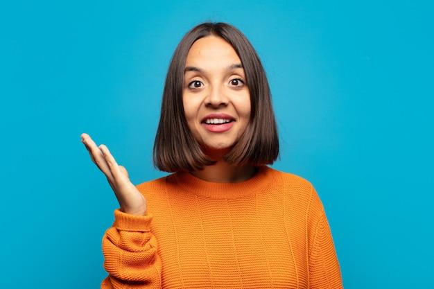 Mulher hispânica se sentindo feliz, surpresa e alegre, sorrindo com atitude positiva, percebendo uma solução ou ideia