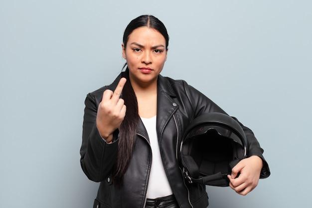 Mulher hispânica se sentindo irritada, irritada, rebelde e agressiva, sacudindo o dedo médio, lutando para trás
