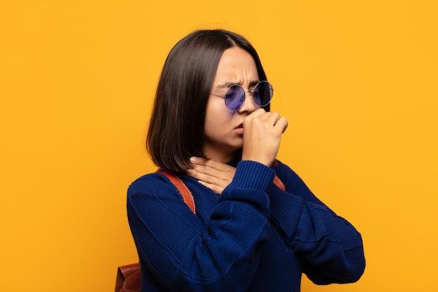 Mulher hispânica se sentindo mal, com dor de garganta e sintomas de gripe, tosse com a boca coberta