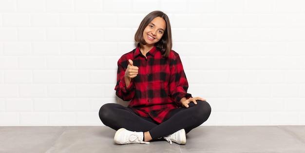 Mulher hispânica se sentindo orgulhosa, despreocupada, confiante e feliz, sorrindo positivamente com o polegar para cima