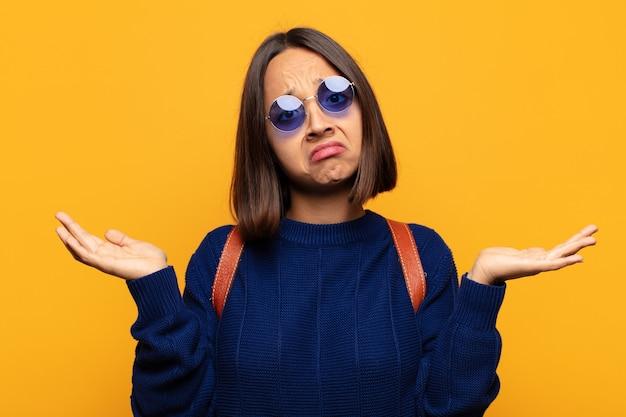 Mulher hispânica se sentindo perplexa e confusa, insegura sobre a resposta ou decisão correta, tentando fazer uma escolha