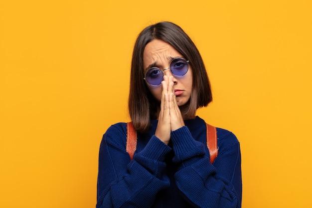 Mulher hispânica se sentindo preocupada, esperançosa e religiosa, orando fielmente com as palmas das mãos pressionadas, implorando perdão