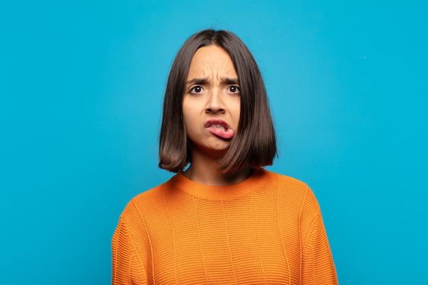 Mulher hispânica se sentindo sem noção, confusa e incerta sobre qual opção escolher, tentando resolver o problema