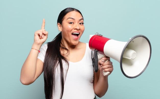 Mulher hispânica se sentindo um gênio feliz e animado depois de realizar uma ideia, levantando o dedo alegremente, eureka!