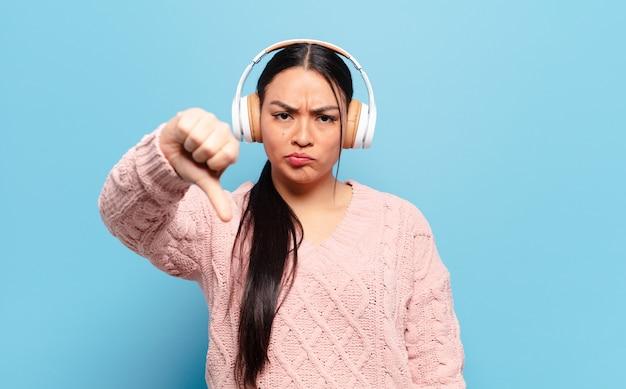 Mulher hispânica se sentindo zangada, irritada, desapontada ou descontente, mostrando o polegar para baixo com um olhar sério