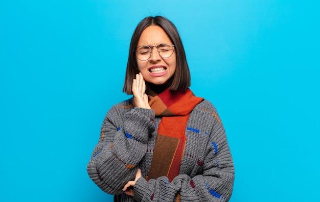 Mulher hispânica segurando a bochecha e sofrendo de dor de dente dolorida, sentindo-se doente, miserável e infeliz, procurando um dentista