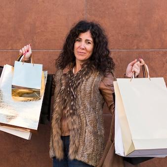 Mulher hispânica, segurando, bolsas para compras
