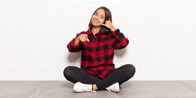 Mulher hispânica sorrindo alegremente e apontando para a câmera enquanto faz um gesto depois de ligar para você, falando ao telefone