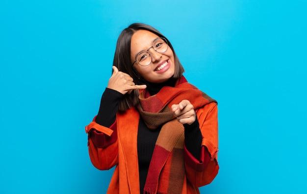 Mulher hispânica sorrindo alegremente e apontando para a frente enquanto faz um gesto para ligar para você, falando ao telefone