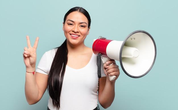 Mulher hispânica sorrindo e parecendo amigável, mostrando o número dois ou o segundo com a mão para a frente, em contagem regressiva