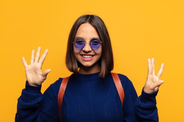 Mulher hispânica sorrindo e parecendo amigável, mostrando o número oito ou oitavo com a mão para a frente, em contagem regressiva