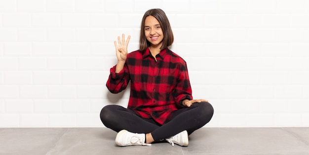 Mulher hispânica sorrindo e parecendo amigável, mostrando o número quatro ou o quarto com a mão para a frente, em contagem regressiva