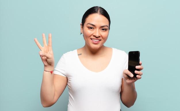 Mulher hispânica sorrindo e parecendo amigável, mostrando o número três ou terceiro com a mão para a frente, em contagem regressiva
