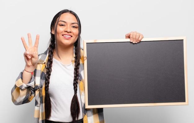Mulher hispânica sorrindo e parecendo amigável, mostrando o número três ou terceiro com a mão para a frente