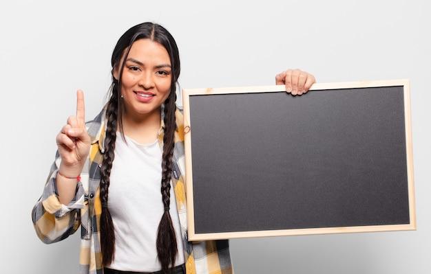 Mulher hispânica sorrindo e parecendo amigável, mostrando o número um ou primeiro com a mão para a frente, em contagem regressiva