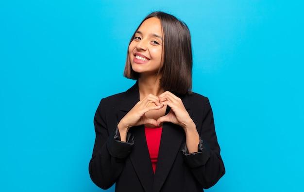 Mulher hispânica sorrindo e se sentindo feliz, fofa, romântica e apaixonada, fazendo formato de coração com as duas mãos