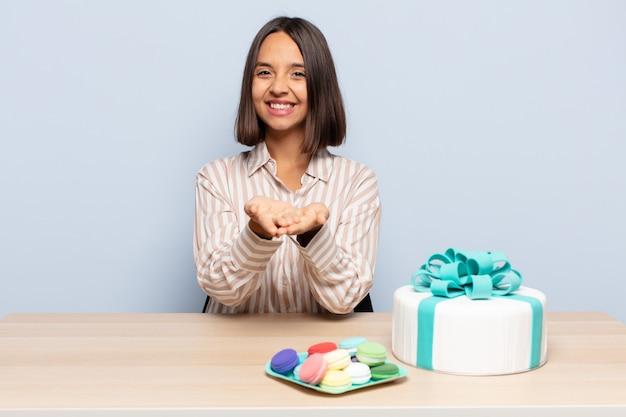 Mulher hispânica sorrindo feliz com um olhar amigável, confiante e positivo, oferecendo e mostrando um objeto ou conceito