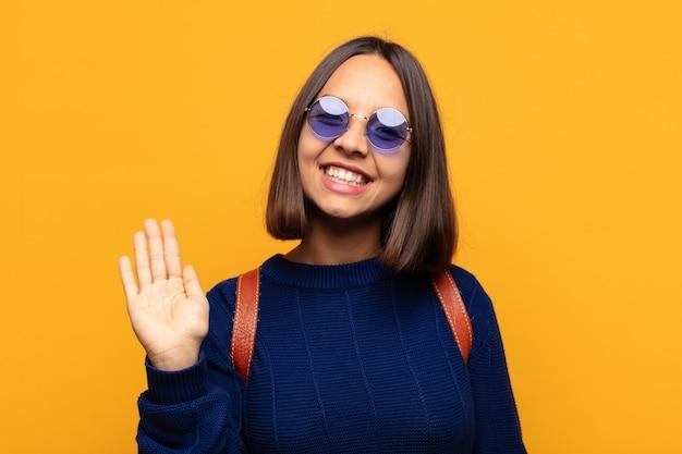 Mulher hispânica sorrindo feliz e alegre, acenando com a mão, dando as boas-vindas e cumprimentando você ou dizendo adeus