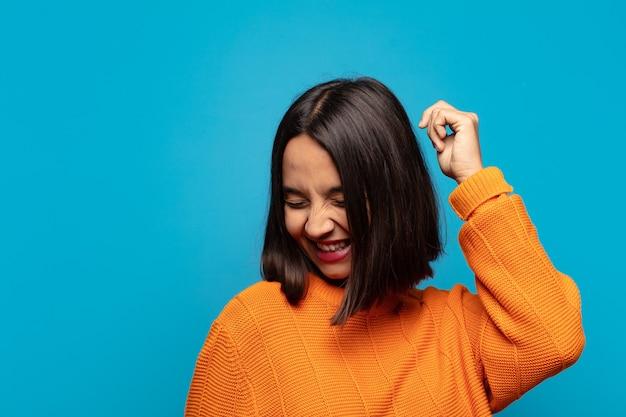 Mulher hispânica sorrindo, sentindo-se despreocupada, relaxada e feliz, dançando e ouvindo música, se divertindo em uma festa