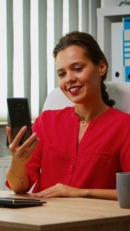 Mulher hispânica, tendo uma reunião on-line no telefone, sentado em um escritório moderno. gerente trabalhando com a equipe de negócios remotamente discutindo bate-papo, conferência virtual, webinar usando tecnologia de internet