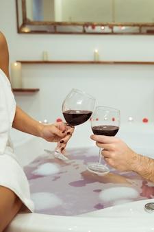 Mulher homem, clanging, copos, de, bebida, perto, água, com, espuma, em, banheira spa