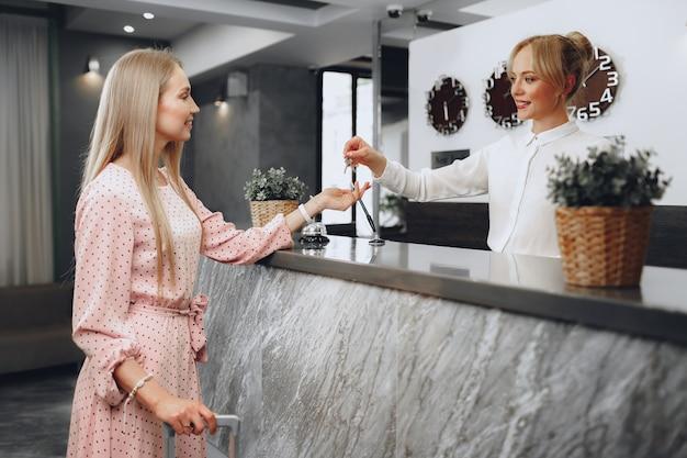 Mulher hospedada em hotel recebendo cartão da recepcionista