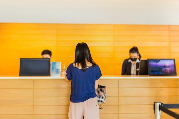 Mulher hóspede check-in com recepcionista no balcão do hotel.