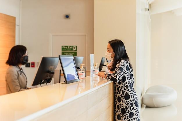 Mulher hóspede do hotel e recepcionista no balcão do hotel, usando máscara médica contra vírus.