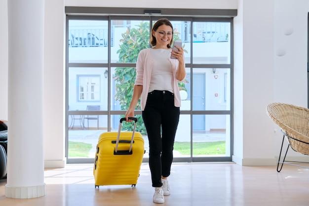 Mulher hóspede do hotel turístico com mala no saguão do hotel usando o smartphone. viagens, férias, lazer, viagem de negócios, pessoas