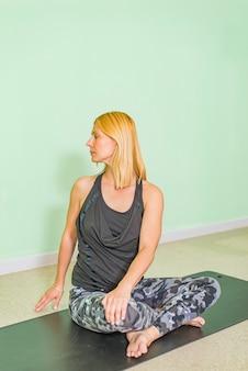 Mulher idade média, fazendo, ioga, ligado, um, esteira exercício, em, estúdio