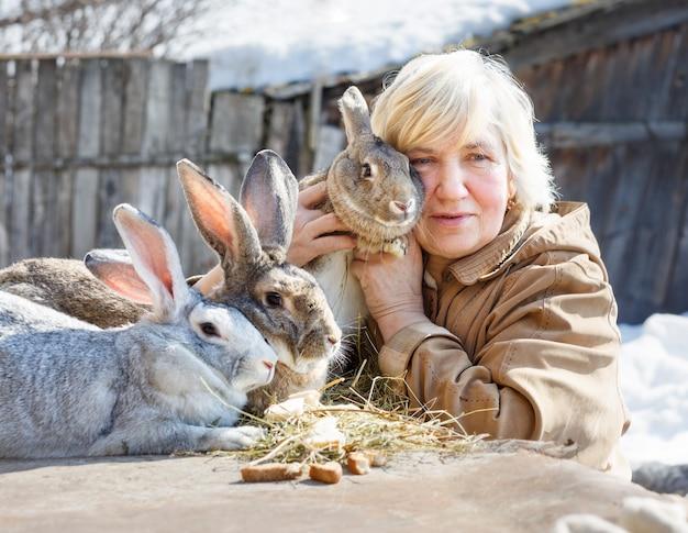 Mulher idosa abraça coelhos gentilmente na fazenda